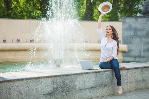 Mooi bedrijfsmeisjesbrunette in een strohoed, met laptop bij een fontein in de straat en haar hand zwaaien