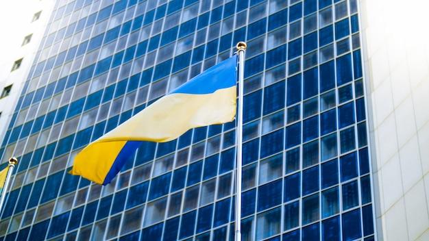 Mooi beeld van de oekraïense vlag die op de wind wappert tegen een hoog modern kantoorgebouw