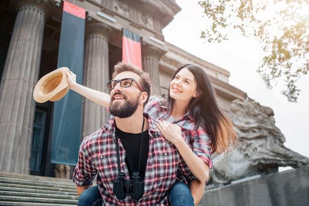Mooi beeld van een jong stel dat samen tijd doorbrengt. ze kijken in dezelfde richting. jonge man houdt vriendin op rug. ze houdt de hoed in de rechterhand.