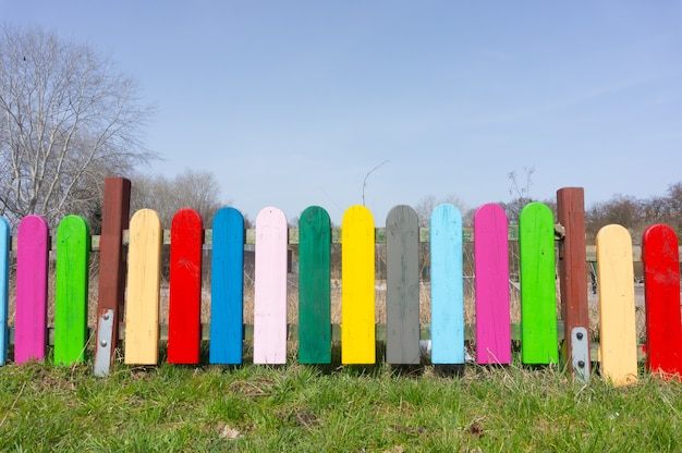 Mooi beeld van kleurrijke houten omheining met gras