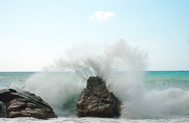 Mooi beeld van sterke golven die op de rotsen op een kust breken