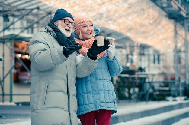 Mooi bejaarde echtpaar in winterjassen die buiten staan met kartonnen kopjes koffie en glimlachen terwijl ze wegkijken. vakantieverlichting achter hun rug om