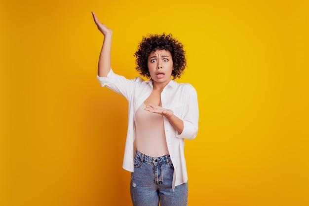 Mooi beledigd meisje steekt handpalm op naar je verbaasd gezicht poseren op gele achtergrond