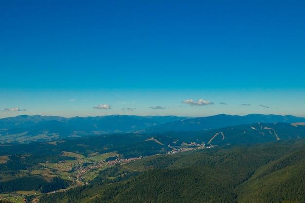 Mooi berglandschap, met bergtoppen bedekt met bos en een bewolkte hemel.
