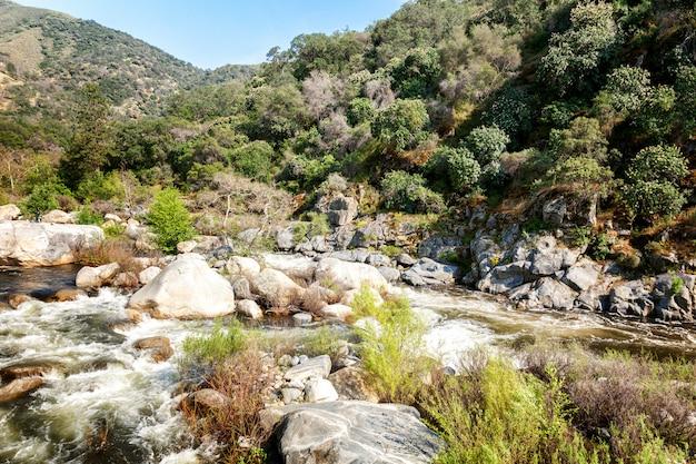 Mooi berglandschap, stroom van bergrivier, stenen, blauwe hemel