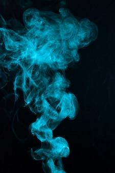 Mooi blauw rookpatroon dat op zwarte achtergrond wordt uitgespreid