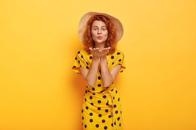 Mooi blauwogig gember vrouwelijk model draagt een strohoed en een modieuze zomerjurk