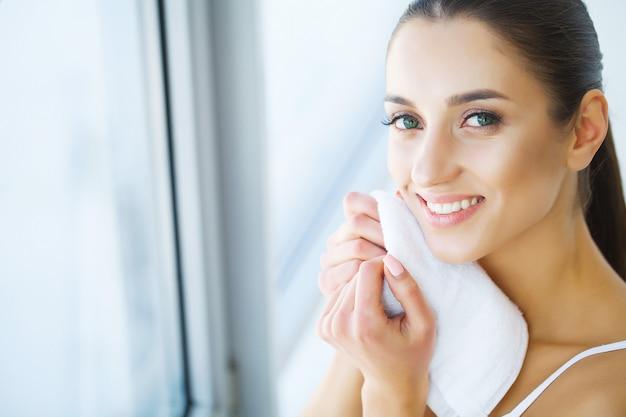 Mooi blij meisje gezicht wassen.