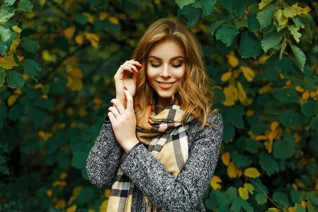 Mooi blij meisje in een vintage sjaal en jas op een geelgroen gebladerte.