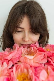 Mooi blij meisje lachend op haar verjaardag, gezicht van een meisje close-up met pioenrozen, valentijnsdag
