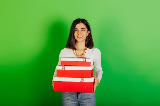 Mooi blij meisje met drie rode geschenkdozen op feestje, verjaardag of vrouwendag concept.