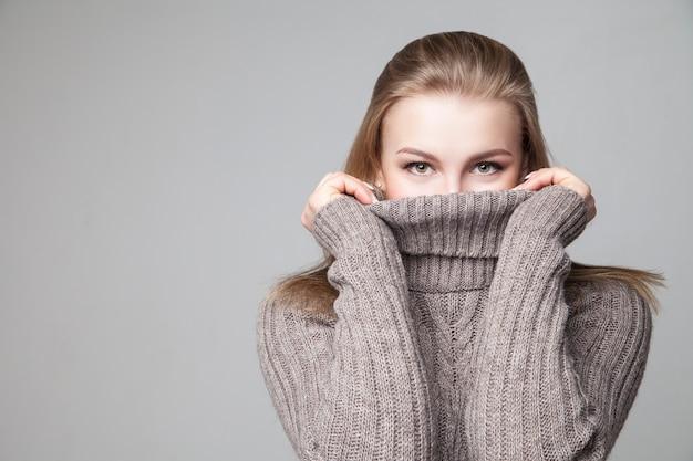 Mooi blond jong meisje draagt wintertrui
