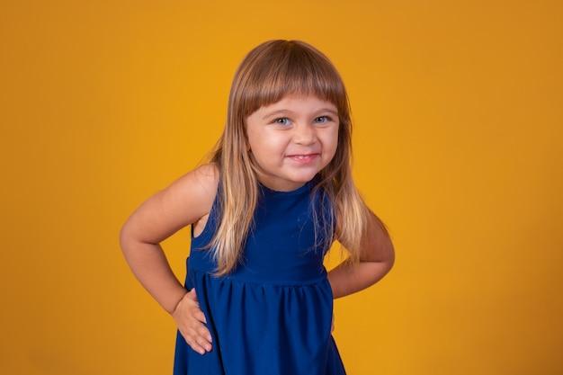 Mooi blond kind meisje glimlachend camera kijken op gele achtergrond met vrije ruimte voor tekst.