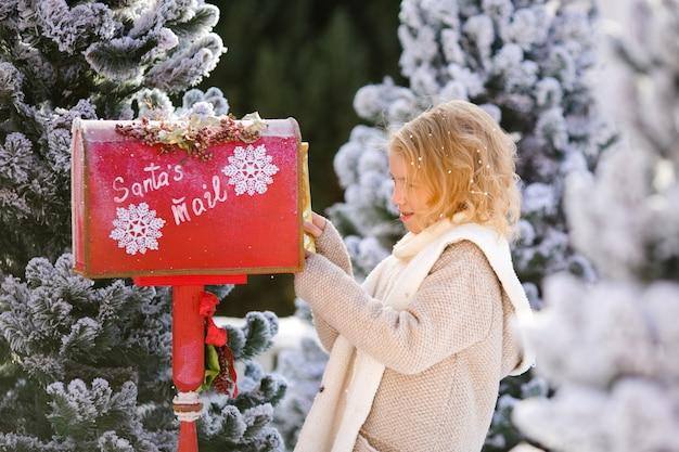 Mooi blond krullend meisje met brief dichtbij de brievenbus van de kerstman