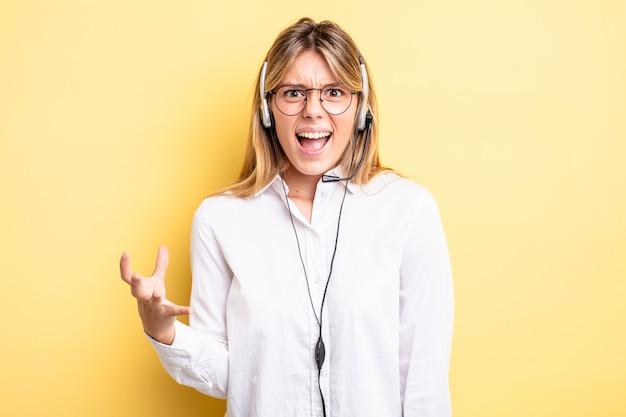 Mooi blond meisje dat boos, geïrriteerd en gefrustreerd kijkt. headset-concept