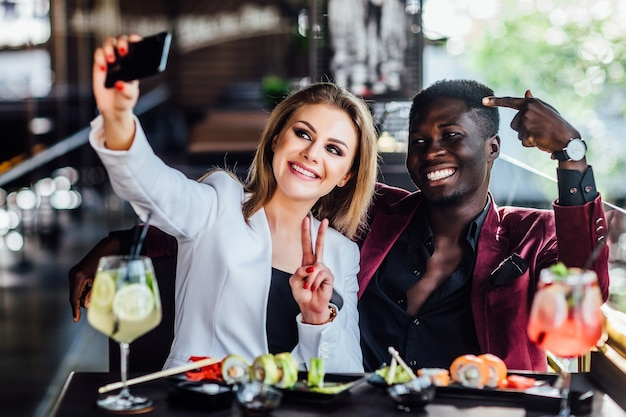Mooi blond meisje dat een foto maakt bij de mobiele telefoon met sushi en mojito. chenese eet, vriendenpaar.
