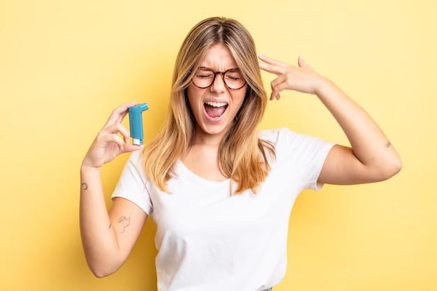 Mooi blond meisje dat er ongelukkig en gestrest uitziet, zelfmoordgebaar dat een pistoolteken maakt. astma-inhalator concept