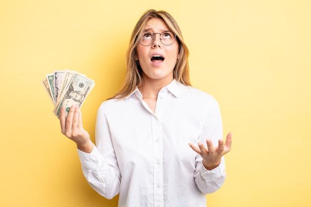 Mooi blond meisje dat er wanhopig, gefrustreerd en gestrest uitziet. dollar biljetten concept