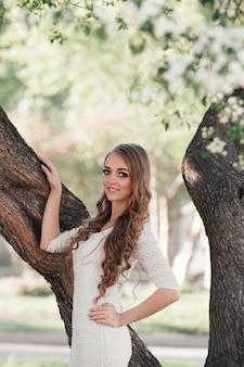 Mooi blond meisje dat in een de lentepark loopt
