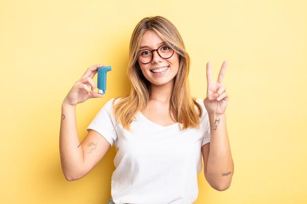 Mooi blond meisje dat lacht en er vriendelijk uitziet, met nummer twee. astma-inhalator concept