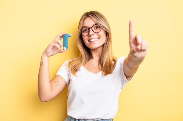 Mooi blond meisje dat trots en vol vertrouwen glimlacht en nummer één maakt. astma-inhalator concept