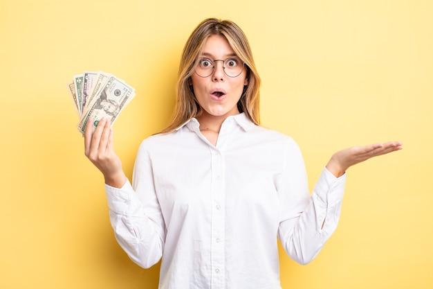 Mooi blond meisje dat verrast en geschokt kijkt, met open mond terwijl ze een voorwerp vasthoudt. dollar biljetten concept