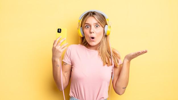Mooi blond meisje dat verrast en geschokt kijkt, met open mond terwijl ze een voorwerp vasthoudt. luisteren muziek concept