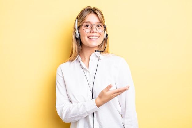 Mooi blond meisje dat vrolijk lacht, zich gelukkig voelt en een concept toont. headset-concept