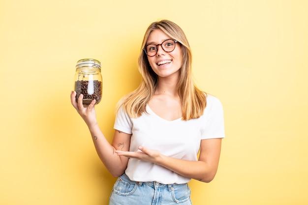 Mooi blond meisje dat vrolijk lacht, zich gelukkig voelt en een concept toont. koffiebonen concept