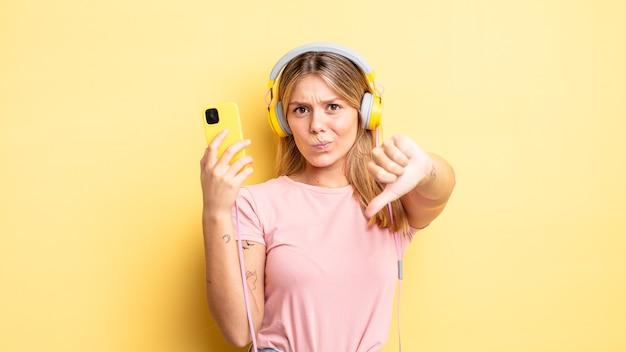 Mooi blond meisje dat zich boos voelt en duimen naar beneden laat zien. luisteren muziek concept