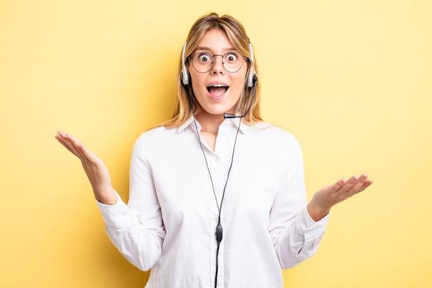 Mooi blond meisje dat zich gelukkig en verbaasd voelt over iets ongelooflijks. headset-concept