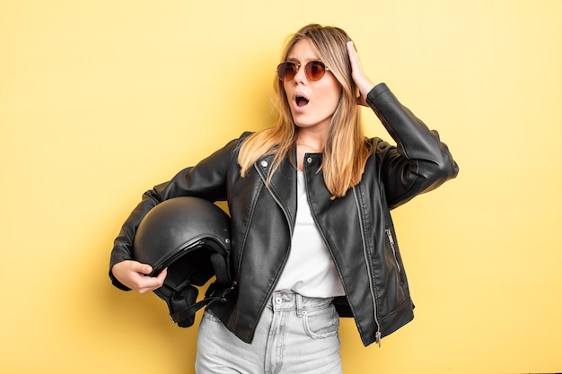 Mooi blond meisje dat zich gelukkig, opgewonden en verrast voelt. motorhelm concept