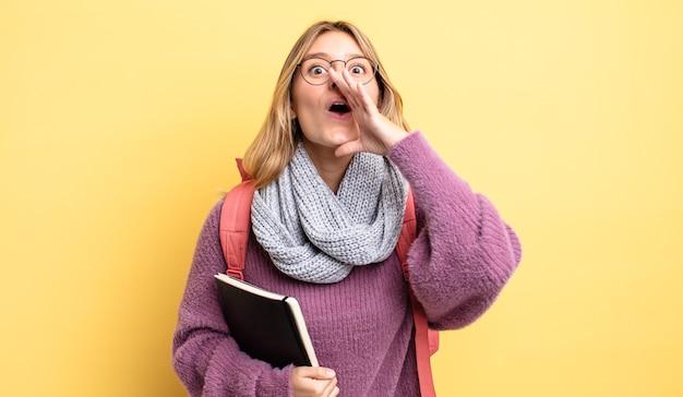 Mooi blond meisje dat zich gelukkig voelt, een grote schreeuw geeft met de handen naast de mond. studentenconcept
