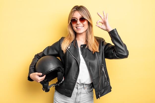 Mooi blond meisje dat zich gelukkig voelt en goedkeuring toont met een goed gebaar. motorhelm concept