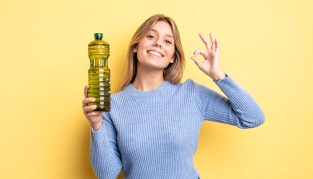 Mooi blond meisje dat zich gelukkig voelt en goedkeuring toont met een goed gebaar. olijfolie concept