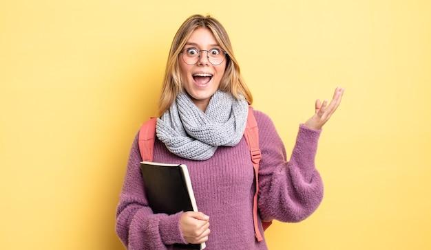 Mooi blond meisje dat zich gelukkig voelt, verrast door het realiseren van een oplossing of idee. studentenconcept
