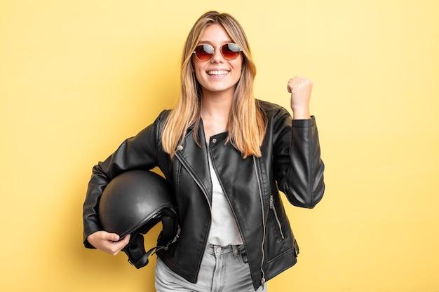 Mooi blond meisje dat zich geschokt voelt, lacht en succes viert. motorhelm concept