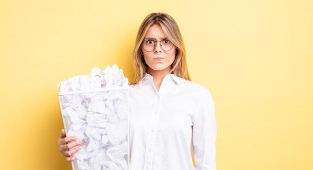 Mooi blond meisje dat zich verdrietig, overstuur of boos voelt en opzij kijkt. papier ballen prullenbak concept