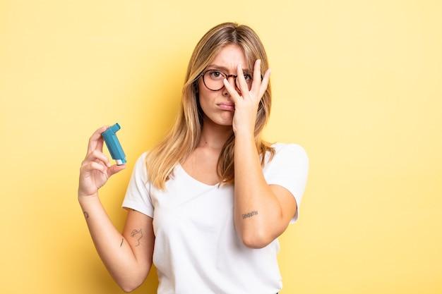Mooi blond meisje dat zich verveeld, gefrustreerd en slaperig voelt na een vermoeiende astma-inhalator concept