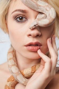 Mooi blond meisje en de slang boa constrictors rond haar gezicht op grijze achtergrond