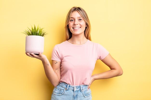 Mooi blond meisje glimlachend gelukkig met een hand op de heup en zelfverzekerd. kamerplant concept