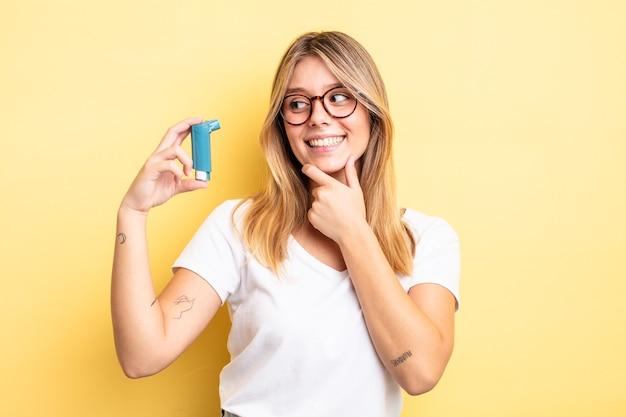 Mooi blond meisje glimlachend met een gelukkige, zelfverzekerde uitdrukking met de hand op de kin. astma-inhalator concept