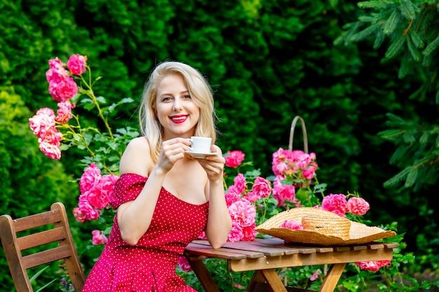 Mooi blond meisje in een rode jurk een kopje koffie drinken in een tuin