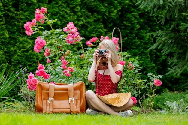 Mooi blond meisje in een rode jurk met vintage camera en koffer in een tuin