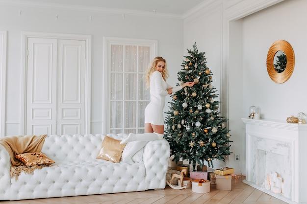 Mooi blond meisje in een sweaterjurk en legging siert een kerstboom