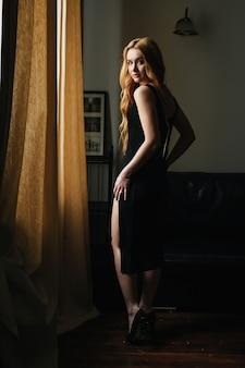Mooi blond meisje in een zwarte jurk staat in het interieur en kijkt uit het raam,
