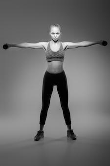 Mooi blond meisje in sportkleding doet oefeningen met halters op een donkere achtergrond
