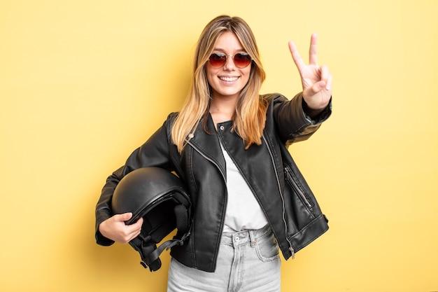 Mooi blond meisje lacht en ziet er gelukkig uit, gebarend overwinning of vrede. motorhelm concept