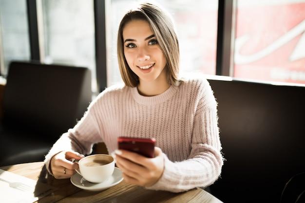 Mooi blond meisje met behulp van haar mobiele telefoon in café tijdens de dagelijkse lunch van de koffierem
