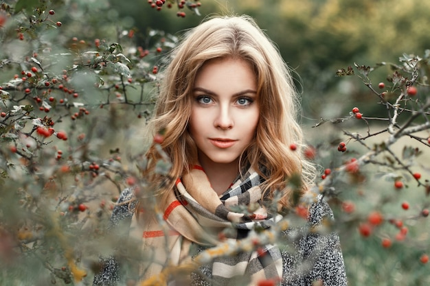 Mooi blond meisje met een gebreide sjaal in de herfstdag in de buurt van een boom.